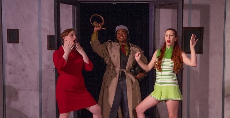 Three drama students on stage posing