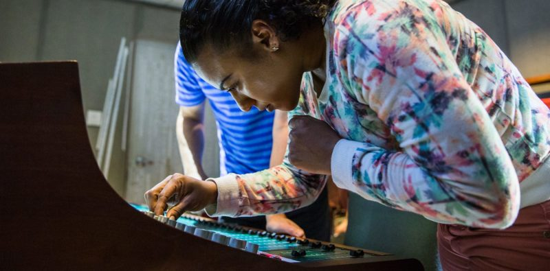 A student adjusting the audio engineering equipment