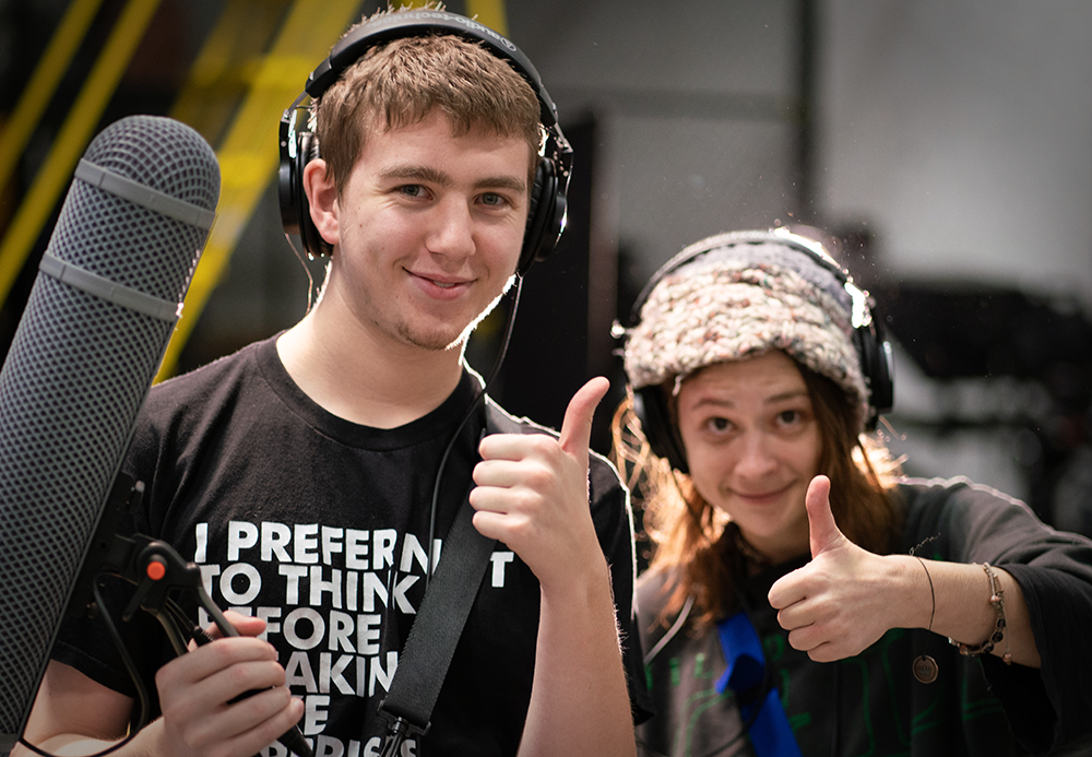 Two RTF students giving thumbs up behind equipment