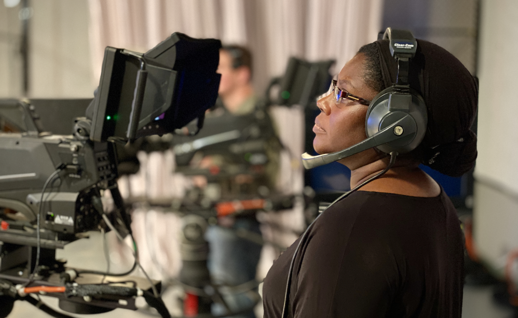 A woman standing behind a camera.